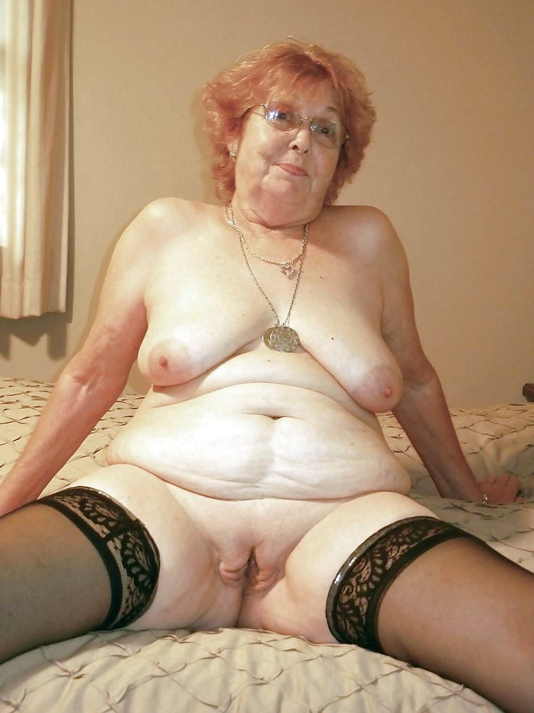 Mature granny buying stuff online with her credit card an her computer on her legs sitting on the couch
