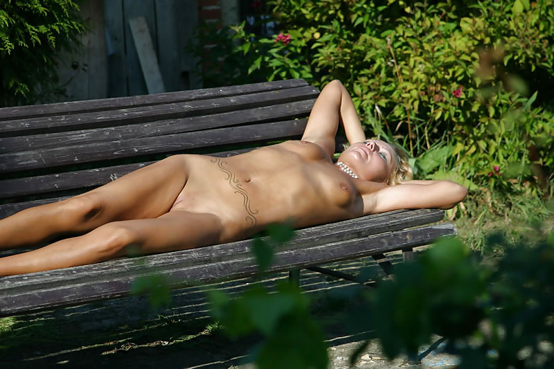 Young woman sunbathing topless on the beach