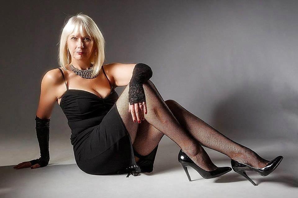 Beautiful mature woman posing in white nightie stock photo